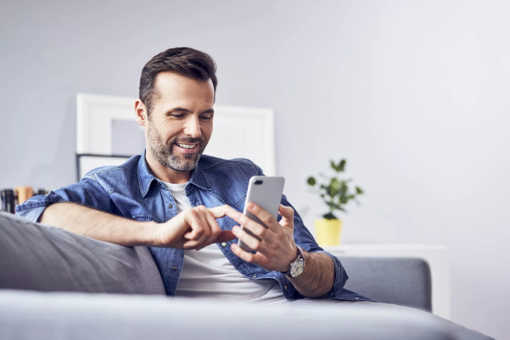 A man looking at his phone and smiling